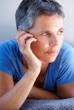 Schließen Sie herauf die schöne reife entspannende und denkende Frau stockfoto