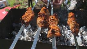 Schließen Sie herauf drehende Fleischaufsteckspindeln Grillen des geschmackvollen Schweinefleischgrills auf Aufsteckspindeln stock video
