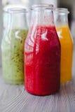 Schließen Sie herauf drei Flaschen Frucht Smoothies Stockfotografie