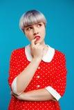 Schließen Sie herauf durchdachtes schönes dollish Mädchen des Porträts mit dem kurzen hellvioletten Haar, das rotes Kleid über bl Lizenzfreies Stockbild