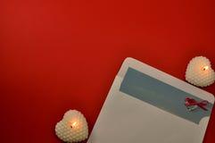 Schließen Sie herauf Ebenenlage des brennenden weißen Kerzenherzens und -umschlags mit Buchstabe- und Diamantring auf rotem Hinte Stockfoto