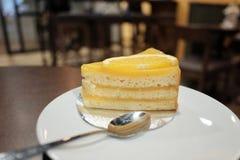 Schließen Sie herauf ein Stück des orange Kuchens in einer weißen Platte mit Stahllöffel auf dinning Tabelle stockfotografie
