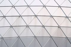 Schließen Sie herauf eine Glasoberfläche eines Dreieckmusters außerhalb eines hohen Gebäudes in der Stadt stockbild