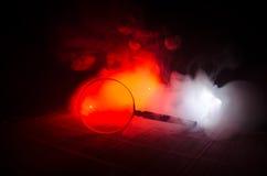 Schließen Sie herauf einzelne Lupe mit dem schwarzen Griff und auf dem Holztisch auf Rauchdunkelheitshintergrund des orange Rotes Lizenzfreie Stockfotos