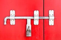 Schließen Sie herauf Eisenverriegelung auf der roten Tür stockbilder