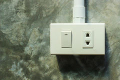 Schließen Sie herauf elektrischen Stecker und Schalter auf grauer Wand Stockfoto