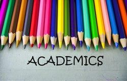 Schließen Sie herauf farbiges Bleistiftschreiben mit AKADEMIKER getrennte alte Bücher Stockfoto