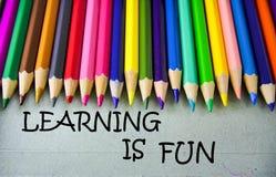 Schließen Sie herauf farbiges Bleistiftschreiben mit dem LERNEN IST SPASS getrennte alte Bücher Lizenzfreies Stockfoto