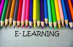 Schließen Sie herauf farbiges Bleistiftschreiben mit E-LEARNING getrennte alte Bücher Lizenzfreie Stockfotos