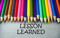 Schließen Sie herauf farbiges Bleistiftschreiben mit GELERNTER LEKTION getrennte alte Bücher Stockfoto