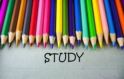 Schließen Sie herauf farbiges Bleistiftschreiben mit STUDIE getrennte alte Bücher Stockfoto