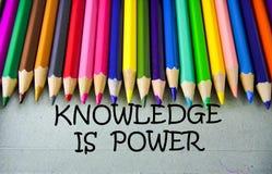 Schließen Sie herauf farbiges Bleistiftschreiben mit WISSEN IST ENERGIE getrennte alte Bücher Stockfotos