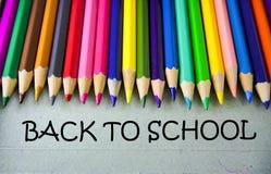 Schließen Sie herauf farbiges Bleistiftschreiben mit ZURÜCK ZU SCHULE getrennte alte Bücher Stockbilder