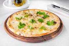 Schließen Sie herauf feinschmeckerische Pizza mit weißen Pilzen Gorgonzola und des porcini, die mit Petersilienblättern auf dem h Stockfotografie