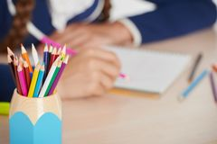 Schließen Sie herauf Foto der Schale mit Bleistiften und Schulmädchen Stockbilder