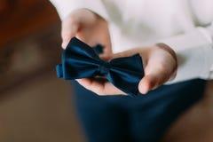Schließen Sie herauf Foto des Geschäftsmannes im weißen Hemd, das seine blaue Fliege in den Händen hält stockbild