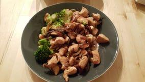 Schließen Sie herauf Foto des Huhns mit brokoli und Acajounüsse in der Platte Stockfoto