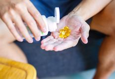Schließen Sie herauf Foto von einer runden gelben Pille in der Hand Mann nimmt Medizin mit Glas Wasser ein Tägliche Norm von Vita lizenzfreie stockfotos