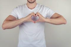 Schließen Sie herauf Fotoporträt des hübschen netten netten attraktiven muskulösen Kerls, der Herz auf dem Kasten macht, der auf  lizenzfreies stockbild