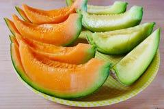 Schließen Sie herauf frische geschnittene Melone mit Platte auf hölzernem Hintergrund am Melonenbauernhof in Furano, Hokkaido, Ja Lizenzfreie Stockfotos