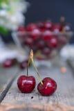 Schließen Sie herauf frische Kirschen mit Glasvase mit Beeren auf dem alten Holztisch Weicher vorgewählter Fokus Rustikales Konze Stockfotos
