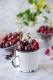 Schließen Sie herauf frische Kirschfrucht im weißen Becher, andere Teller mit Beeren und Vase mit Jasminblumen auf der hellen Mar Stockbild