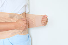 Schließen Sie herauf geduldige lumbale Spondylose mit LS-Unterstützung auf weißem b Stockbilder