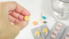 Schließen Sie herauf gelbe Medizin mit der Frauenhand, die eine Pille und glas nimmt Stockbild