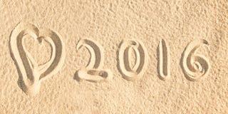 Schließen Sie herauf 2016 geschrieben in den Sand eines Strandes Stockbild