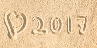 Schließen Sie herauf 2017 geschrieben in den Sand eines Strandes Lizenzfreie Stockfotos