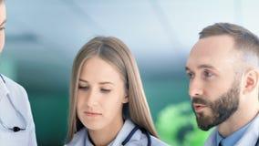 Schließen Sie herauf Gesicht des europäischen medizinischer Mann- und Frauenspezialisten, der lebhaft etwas bespricht stock video