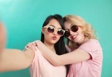 Schließen Sie herauf Gesichtsporträt von den glücklichen multiethnischen Freundinnen, die über Blau lokalisiert werden Stockbild