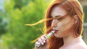 Schließen Sie herauf Gesichtsprofil, rauchende Ezigarette des Mädchens mit Dampf Langsame Bewegung stock footage