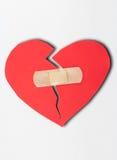 Schließen Sie herauf Gips und tapezieren Sie defektes Herz auf weißem Hintergrund Stockbild