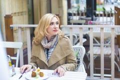 Schließen Sie herauf glückliche erwachsene blonde Frau im Freiencafé, das d untersucht Stockbilder