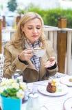 Schließen Sie herauf glückliche erwachsene blonde Frau mit Tasse Kaffee Lizenzfreie Stockbilder