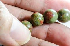 Schließen Sie herauf glücklichen Steinedelstein an Hand stockfotografie