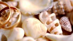 Schließen Sie herauf goldene Eheringe auf Oberteilen Makro stock video footage