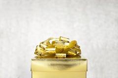 Schließen Sie herauf goldenen Präsentkarton mit großem Bogen an bokeh weißem Unschärfe-BAC Stockbild