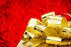 Schließen Sie herauf goldenen Präsentkarton mit großem Bogen an bokeh weißem Unschärfe-BAC Lizenzfreies Stockfoto