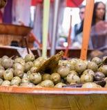 Schließen Sie herauf grüne Oliven in einer hölzernen Schüssel Stockfotos