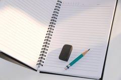 Schließen Sie herauf grünen Bleistift und schwarzen den Radiergummi, die auf ein Notizbuch gesetzt wird Lizenzfreie Stockfotos