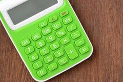 Schließen Sie herauf grünen Taschenrechner auf hölzernem stockfotos