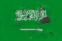 Schließen Sie herauf grungy, schädigende und verwitterte Saudi-Arabien Flagge auf der Wand, die weg von der Farbe abzieht, um Inn stockbild