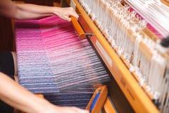 Schließen Sie herauf Hände der Frau spinnendes purpurrotes und weißes Muster auf Webstuhl Stockfoto