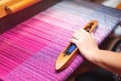 Schließen Sie herauf Hände der Frau spinnendes purpurrotes und weißes Muster auf Webstuhl Lizenzfreies Stockfoto
