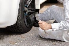 Schließen Sie herauf Hände des Berufsmechanikers im weißen einheitlichen haltenen Schlüssel, der zur Reparatur des Autos an der G Stockfotos