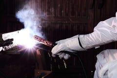 Schließen Sie herauf Hände des Handwerkerschweißers mit Schweißensmetallstahl der Fackel und der Schutzhandschuhe mit Funken in d Lizenzfreies Stockbild