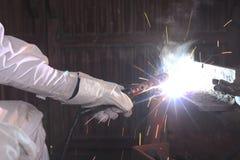 Schließen Sie herauf Hände des Industriearbeiters mit der Fackel und Schutzhandschuhen, die Stahl mit Funken in der Fabrik schwei Stockfotografie
