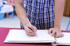 Schließen Sie herauf Hände des Mannschreibens auf Gedächtnisgastbuch für die Segnung des Wortes, um sich zu pflegen und der Braut Stockfoto